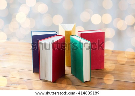 education, school, literature, reading and knowledge concept - close up of books on wooden table over holidays lights background - stock photo