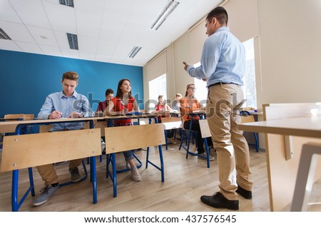 education, school, teaching, technology and people concept - group of happy students and teacher with tablet pc computer - stock photo