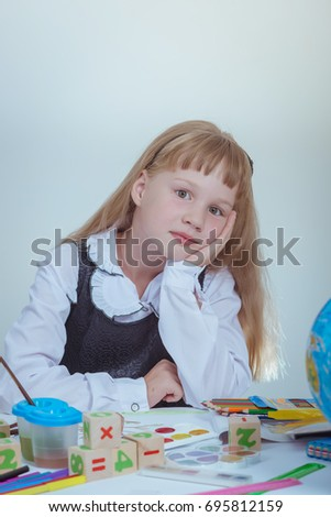 education. Schoolgirl with books sitting at table