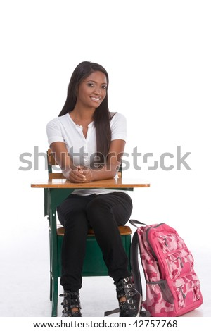 education series - Friendly ethnic black woman high school student sitting by school desk with pink backpack by her legs - stock photo