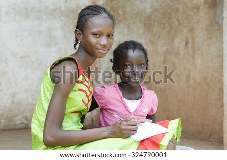 Education Symbol: Two Gorgeous African girls Learning their lessons on an exercise book outside of a classroom in the public school of Bamako, Mali. Close-up picture with two black children. - stock photo