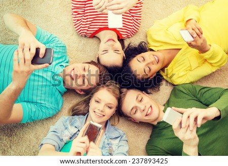 education, technology and happiness concept - group of young smiling people lying down on floor in circle with smartphones - stock photo