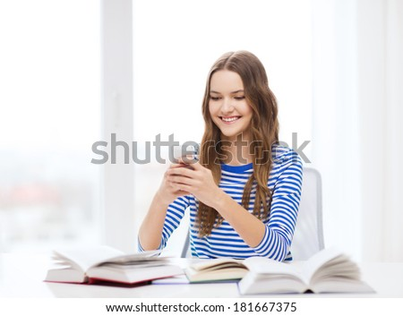 education, technology and home concept - happy smiling student girl with smartphone and books - stock photo