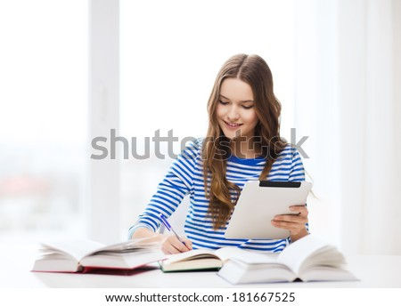 education, technology and home concept - happy smiling student girl with teablet pc computer and books at home - stock photo
