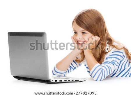 education, technology and internet concept - smiling little student girl with laptop computer lying on the floor