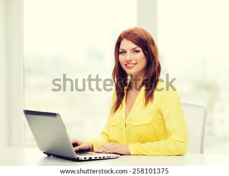 education, technology and internet concept - smiling student with laptop computer at school - stock photo