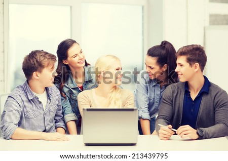 education, technology and internet concept - smiling students with laptop at school looking at each other