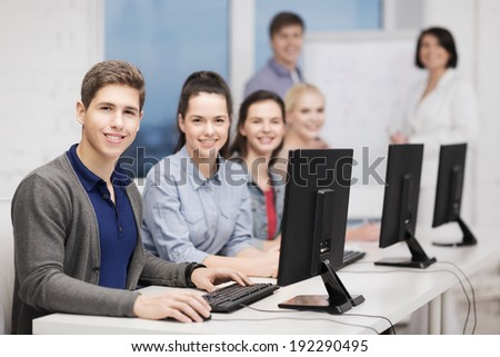 education, technology and internet concept - students with computer monitor at school - stock photo