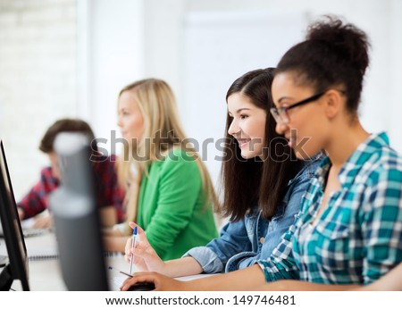 education, technology and internet - students with computers studying at school - stock photo