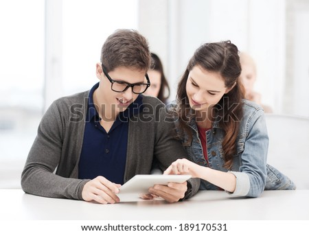 education, technology and internet - two smiling students looking at tablet pc in lecture at school - stock photo