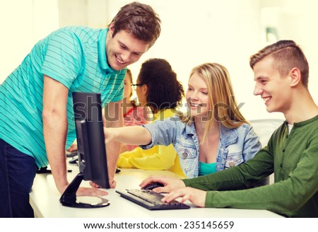 education, technology and school concept - smiling students in computer class at school - stock photo