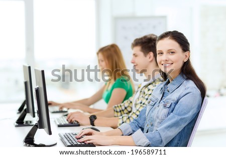 education, technology and school concept - three smiling students in computer class