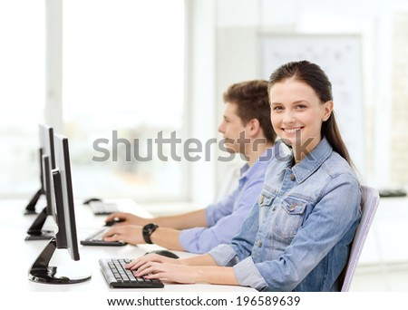 education, technology and school concept - two smiling students in computer class
