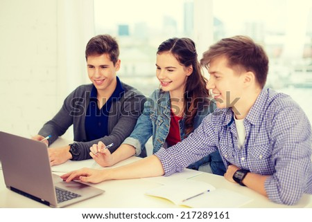 education, technology, school and internet concept - three smiling students with laptop and notebooks at school