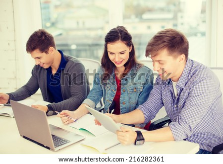 education, technology, school and internet concept - three smiling students with laptop, tablet pc and notebooks at school