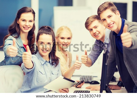 education, techology and internet concept - group of smiling students with computer monitor and tablet pc - stock photo