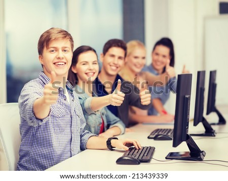 education, techology and internet concept - group of smiling students with computer monitor showing thumbs up at school - stock photo