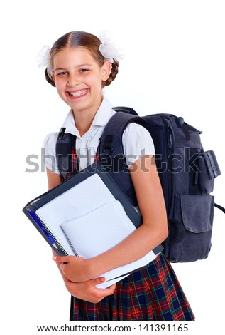 Education theme. Joyful schoolgirl smiling happily with backpack holding book