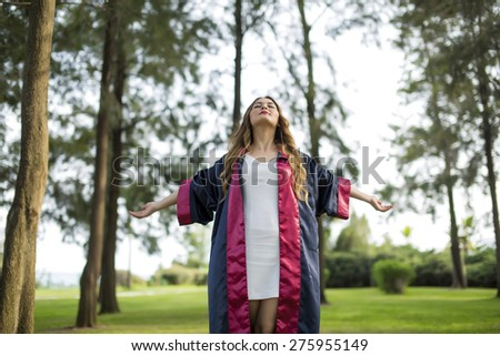 Education theme of happy graduate student girl outdoors - stock photo