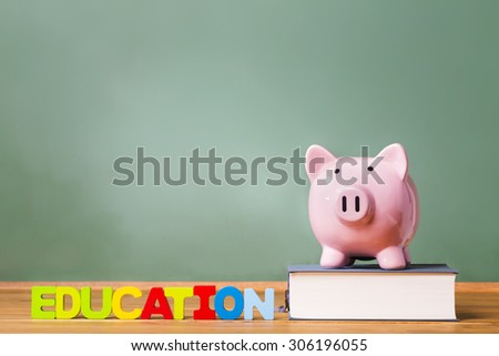 Education theme with textbooks and piggy bank and green chalkboard background - stock photo