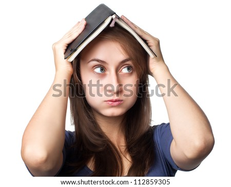 Education. Tired girl holds a notebook on her head on a white background - stock photo