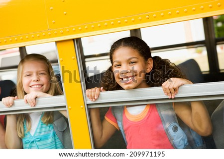 Education: Two Friends Look Out Of School Bus Windows - stock photo
