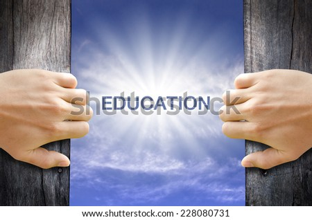 Education word floating and shining in the sky while two hands opening an old wooden door. - stock photo