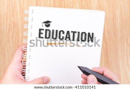 Education word on white ring binder notebook with hand holding pencil on wood table,Learning concept. - stock photo