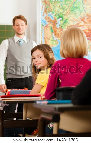 Education - Young teacher with pupil in his form of the elementary or primary school teaching - stock photo