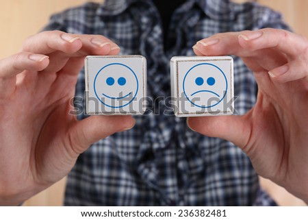 Educational cubes with smiles in hands, close-up - stock photo