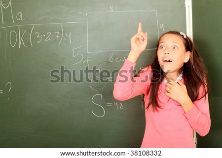 Educational theme: funny schoolgirl in a classroom. - stock photo