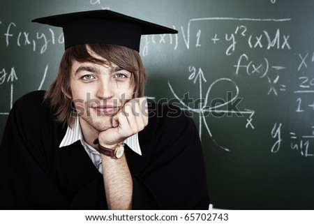 Educational theme: graduating student in academic gown in a classroom. - stock photo