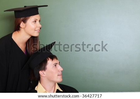 Educational theme: graduating students in academic gown in a classroom. - stock photo