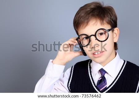 Educational theme: portrait of a schoolboy. Studio shot over grey background. - stock photo
