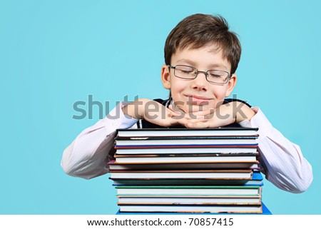 Educational theme: portrait of a schoolboy with books. Over grey background. - stock photo
