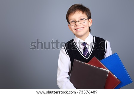 Educational theme: portrait of a schoolboy with books. Studio shot over grey background. - stock photo