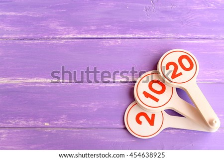 Educational toy for teaching kids numbers. Numbers two, ten, twenty. Early child development. How teach to recognize children the numbers. Purple wooden background with blank place for text  - stock photo