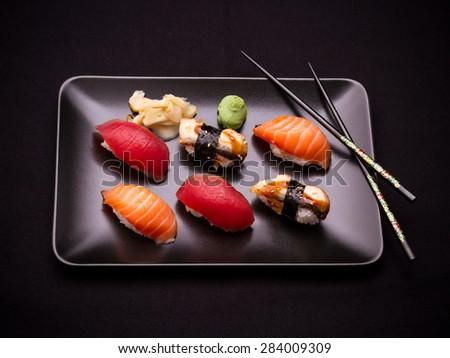 Eel, salmon and tuna sushi with chopsticks, dark background - stock photo