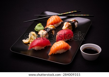 Eel, salmon and tuna sushi with chopsticks, dark background - stock photo