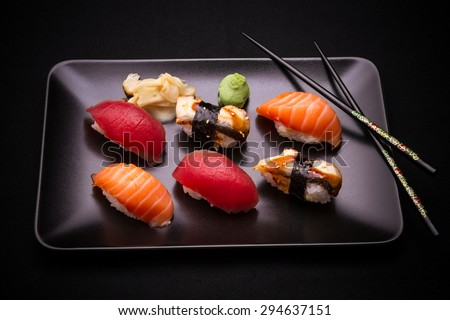 Eel, salmon and tuna sushi with chopsticks, dark background, top view - stock photo