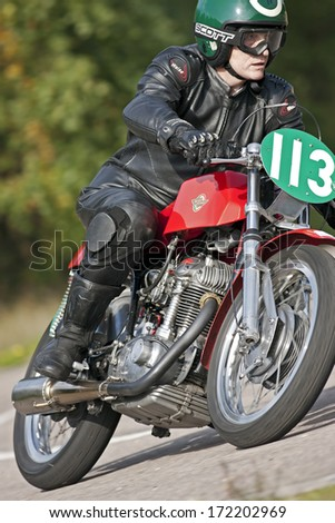 EELMORE, UK - SEPTEMBER 29: An unnamed rider competing in the VMCC Eelmore sprint race takes the top corner of the circuit at speed on his vintage Ducati  motorcycle on September 29, 2013 in Eelmore