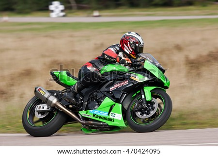 EELMORE, UK - SEPTEMBER 29: An unnamed rider competing in the VMCC Eelmore sprint race takes the top corner of the circuit at speed on his Kawasaki ZX6R motorcycle on September 29, 2013 in Eelmore