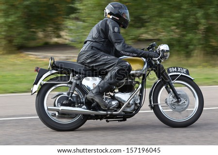 EELMORE, UK - SEPTEMBER 29: An unnamed rider takes his vintage Triumph motorcycle  out of the apex of a bend at the VMCC Ossie Neal Memorial Sprint race on September 29, 2013 in Eelmore - stock photo