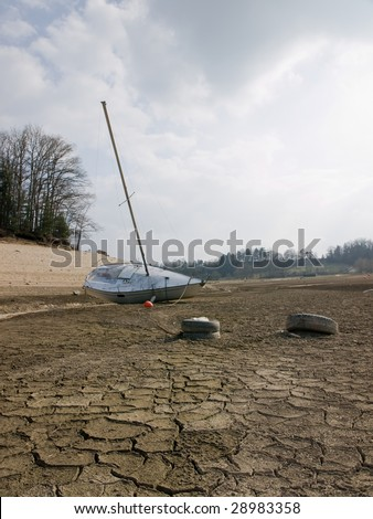 Effect of global warming: a boat on the bottom of a dry lakebed. Dried, cracked earth is the consequence of the climate change and global warming. - stock photo