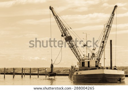 Effect vintage. Dredger ship navy working to clean a navigation channel - stock photo