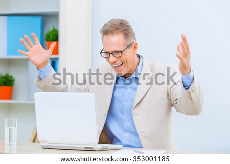 Effective work.  Handsome businessman is expressing happy emotions at his desk. - stock photo