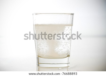 Effervescent Antacid Tablet in Glass of Water - stock photo