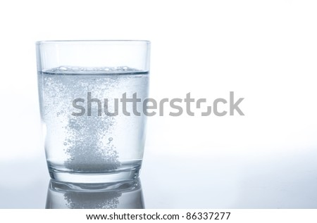 effervescent bubbles from a tablet in water - stock photo