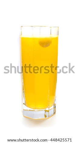 Effervescent orange tablet dissolving with bubbles in glass of water - stock photo