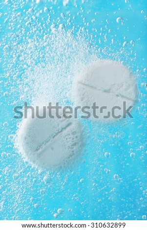 Effervescent painkiller tablets in water, closeup